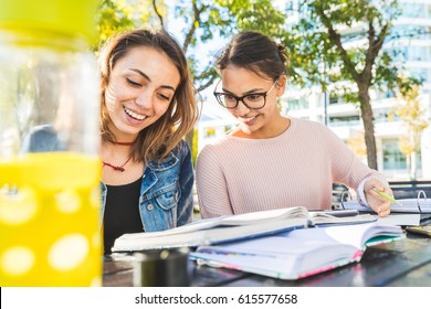 Girls studying together at park. Happy best friends with books having fun while studying. Friendship and lifestyle concepts.