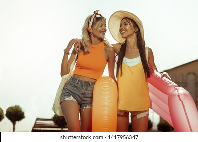 Girls with swim rings. Happy alluring dazzling beaming radiant cheerful lovely joyous girls wearing beach clothing hugging and holding swimming rings in hands.