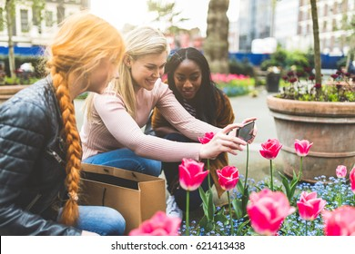 Girls taking photos of tulip flowers in London. Multiracial group of women looking at beautiful flowers at park and taking photos with smart phone. Nature and lifestyle concepts