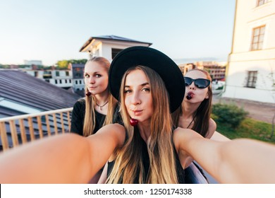 Girls are taking self portrait by camera or phone. Funny and smiling girls. Women friendship. Pretty female friends. Summer young vibes