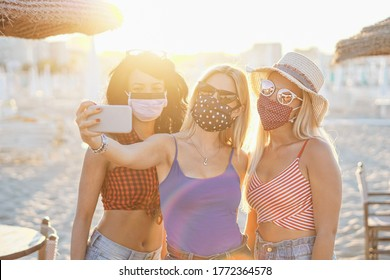 Girls taking a selfie with face mask outside for coronavirus protection - Teenagers in vacation at a beach enjoying the sunset - Multiracial youth having fun together - Young people using smartphone