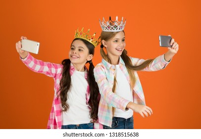 Girls taking selfie photo smartphone camera. Spoiled children concept. Egocentric princess. Kids wear golden crowns symbol princess. Warning signs of spoiled child. Avoid raising spoiled kids.