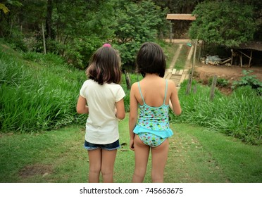 Girls talking behind the back in the countryside