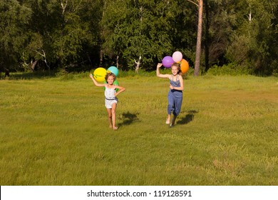 Girls ten and eight years running across the field with balloons
