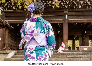 Girls in traditional clothes at the entrance to the Chion-In Temple in Kyoto, Japan
