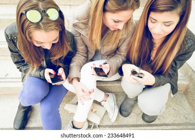 Girls typing on mobile phones - Three friends holding smart phones and chatting - Students sitting outdoors on stairs and talking