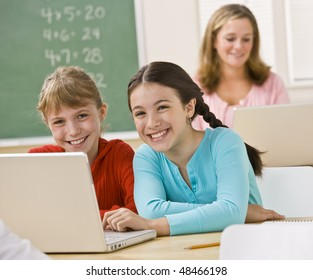 Girls using laptop in classroom
