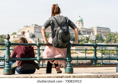 Girls waiting for tram Budapest, Hungary - September 27, 2017: Two young women leaning against a railing by the Danube river in Budapest, resting and waiting for a tram. Buda Castle in the background.