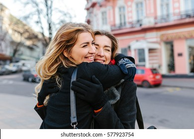 girls walk and lovely spend time. They are glad to see each other and embrace. They have very good mood. On the street pleasant weather.