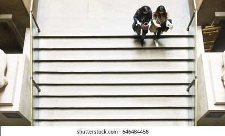 the girls walk on the top of public stair at top aerial view.