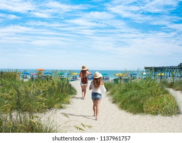 Girls walking on the beach on summer vacation.  Beach chairs and parasols on beautiful white sand in the background.  Myrtle Beach, South Carolina, USA.