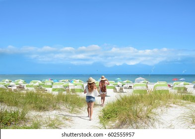 Girls walking on the beach on summer vacation.  Beach chairs and parasols on beautiful white sand in the background.  Gulf of Mexico, Clearwater Beach, Florida, USA.