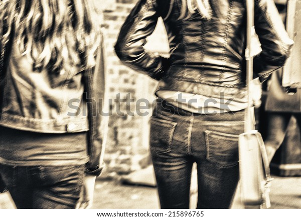 Girls walking on the street, back view. Blurred city scene.