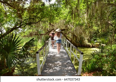 Girls walking  under oak tree branches  with spanish moss on romantic bridge . Magnolia Plantation and Gardens,Charleston ,South Carolina ,USA.