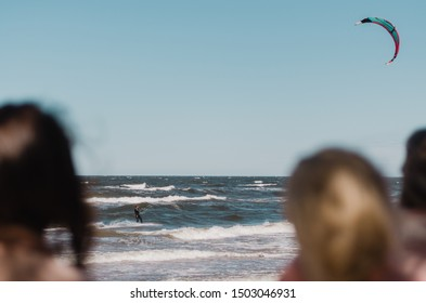 Girls watching a kitesurfer catching big waves in the Baltic sea