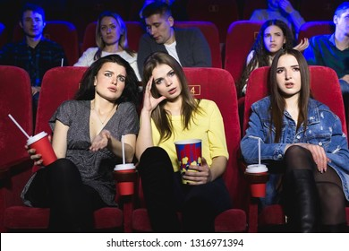 Girls watching a really boring movie at the cinema theater. Bad film