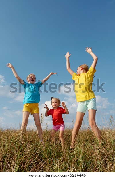 Girls wearing colorful t-shirts playing on a meadow