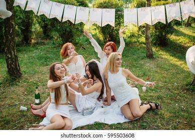 Girls wearing on white dresses having fun on hen party.
