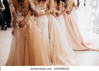 girls in wedding dresses are standing with their backs and arms hugging their waists