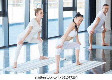 girls in white clothes doing sumo pose (rudrasana) with instructor indoors