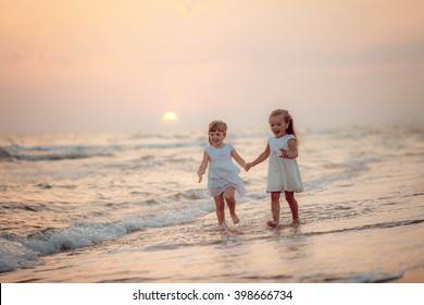 Girls in white dresses are on the beach at sunset