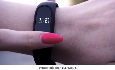 The girls wore a fitness bracelet. Girl checks pulse on fitness bracelet or activity tracker pedometer on wrist, sport, technology and healthy lifestyle concept, close up. Looks at the pedometer