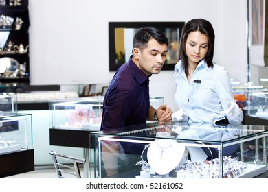 The girl-seller shows to the visitor assortment in jeweller shop