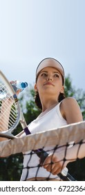 The girl-winner looks at the competitor on tennis & drink water