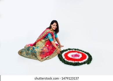 girl/woman making flower rangoli for hindu festival celebration, sitting over white background, selective focus