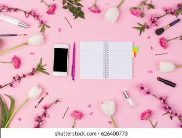 Girly, beauty blog, spring, concept. Feminine blogger or freelancer workspace with notebook, phone, perfume, sakura, rose, tulips flowers and women's accessories on pink background. flat lay, top view