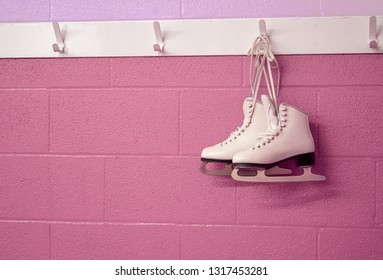 Girly figure skates hanging in pastel background with copy space