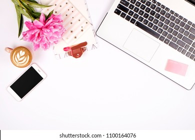 Girly office desktop with black & white laptop keyboard, pink peony flowers bouquet, cup of coffee, blank screen mobile cell phone, smartphone, pen, supplies. Background flat lay, copy space, close up