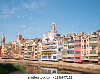 GIRONA, CATALONIA / SPAIN - JUNE 2018: Colorful houses and Saint Mary Cathedral at Onyar River in Girona, Catalonia, Spain.