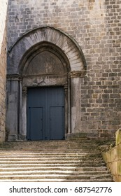 GIRONA, SPAIN - 29 JUNE 2017 - Arched entrance from the north side of Basilica of Sant Feliu. Girona's first cathedral until the 10th century in Girona, Catalonia, Spain