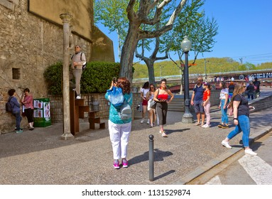 GIRONA, SPAIN - APRIL 20, 2018: Tourists near Romanesque column with climbing Lioness, which is a symbol of Girona