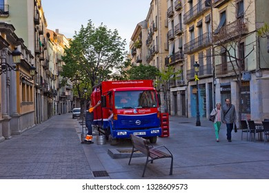 Girona, Spain - April 20, 2018: Early morning in the center of old town with people and distribution vehicle