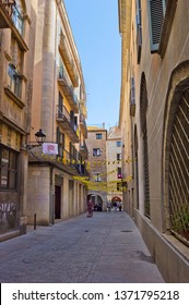 Girona, Spain - April 20, 2018: Narrow street with medieval houses in old quarter of the city