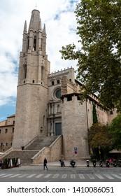 Girona, Spain - September 24 2018: The Collegiate Church of Sant Felix, as seen from the street, Girona, Spain. Pujada de Sant Feliu. Motor bikes parked out front