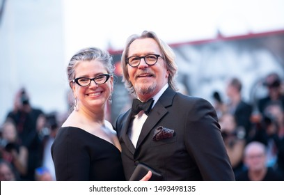 """Gisele Schmidt and Gary Oldman walk the red carpet ahead of the """"The Laundromat"""" screening during the 76th Venice Film Festival at Sala Grande on September 01, 2019 in Venice, Italy."""