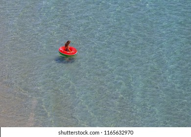 GITHIO, LAKONIA - JULY 2017: Beautiful girl having fun in a red melon shaped buoy floating onto the sea