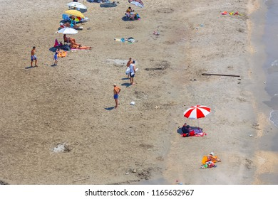 GITHIO, LAKONIA - JULY 2017: Various age and sex people having fun at the sandy beach near Githio, Lakonia, Greece