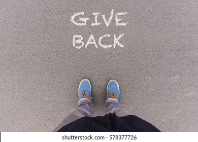 Give Back text on asphalt ground, feet and shoes on floor, personal perspective footsie concept
