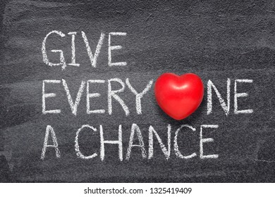give everyone a chance phrase written on chalkboard with red heart symbol
