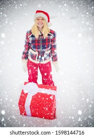Give gift. Christmas Woman holding a huge gift box - full length. Happy woman standing on white snow background and holding a giant red gift box with both hands