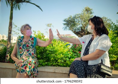 Give me air five - says an elderly woman to a caregiver.  Both in face protective masks sitting in a park area nearby a house.