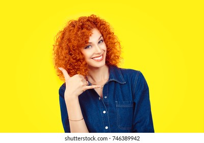 Give me a call. Closeup portrait redhead curly hair woman excited happy student making showing call me gesture sign with hand shaped like phone on yellow background. Positive emotion face expression