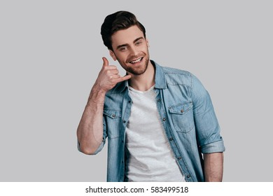 Give me a call! Good looking young man in blue jeans shirt gesturing and looking at camera while standing against grey background