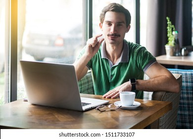 Give me a few more. Young funny businessman in green t-shirt sitting and looking at camera and asking to give him more time. business concept. indoor shot near big window at daytime.