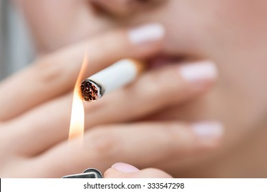 Give me fire. Close up of cigarette in hands of unhealthy girl lighting it and smoking