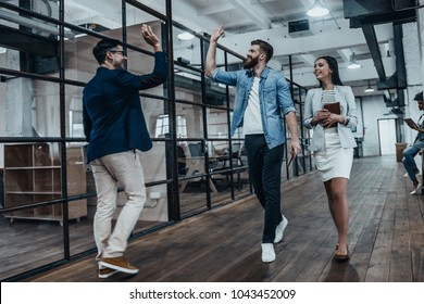 Give me five! Full length of two cheerful young business people giving high-five while their colleague looking at them and smiling